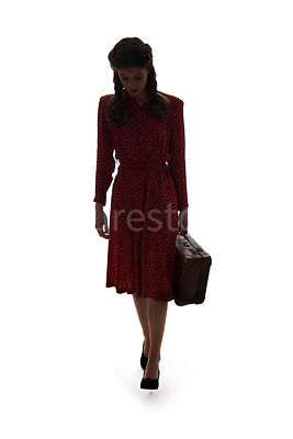 A silhouette of a 1940's woman in a red dress, walking with a suitcase – shot from eye-level.