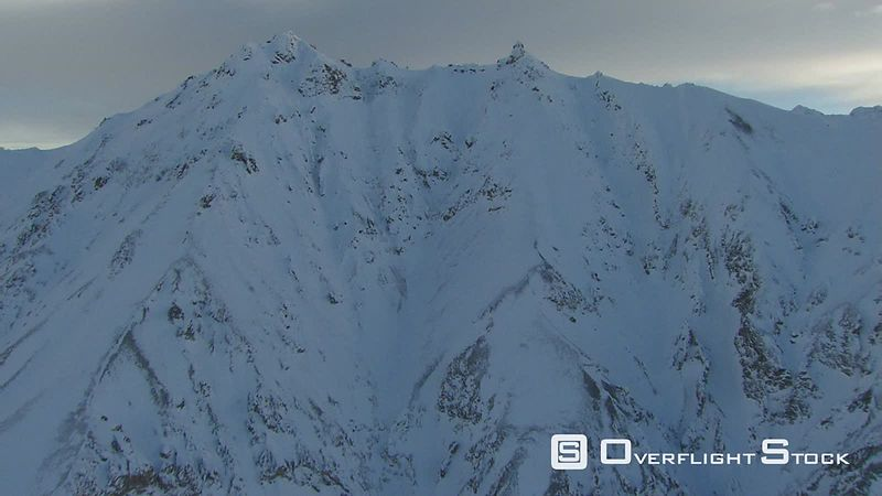 Flying over snowy mountain summit in Alaska