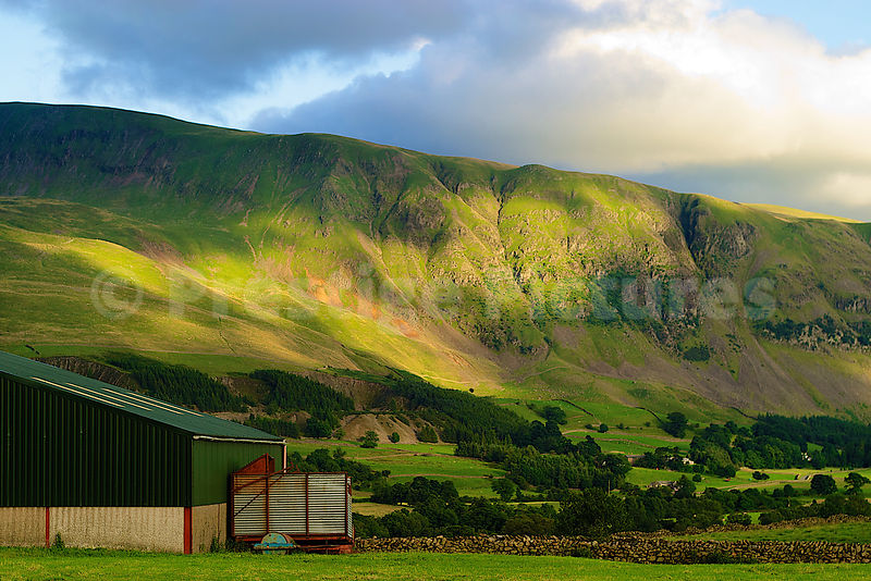 Farm Building with a Sunlit Rugged Hillside Behind