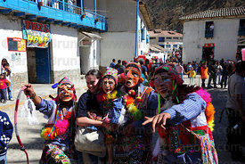 Masked Maqtas dancers with tourist at Virgen del Carmen festival , Paucartambo , Peru