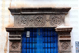 Detail of Christogram (centre) and other stone carvings on lintel of colonial doorway, Cusco, Peru