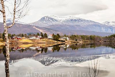 Small rural community in Northern Norway reflected in the fjord with the snow-capped mountains
