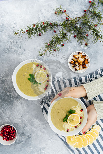 A woman holding a bowl of cheesy broccoli soup photographed from top view. Pomegranate arils, lemon slices, croutons and pine tree branches accompany.