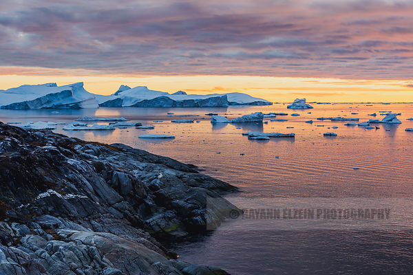 Sunset at the Ilulissat Icefjord in West Greenland with silhouettes of people in kayaks among the icebergs