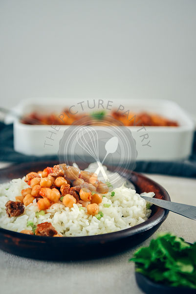 Simple fried rice topped with garbanzo beans and beef stew in a dark ceramic dish on a dinner table photographed from front view. A casserole pan and herbs accompany.