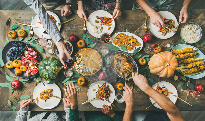 Friends feasting at Thanksgiving Day table with turkey, top view