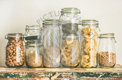Uncooked cereals, grains, beans and pasta on rustic table
