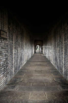 An atmospheric image of an empty brick passage at an old Victorian cemetary.