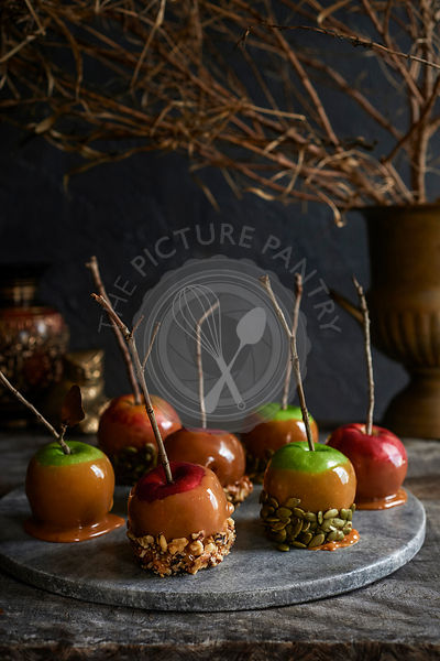 Marble tray full of caramel apples with stick handles covered in nuts and seeds. Moody fall foliage in the background.