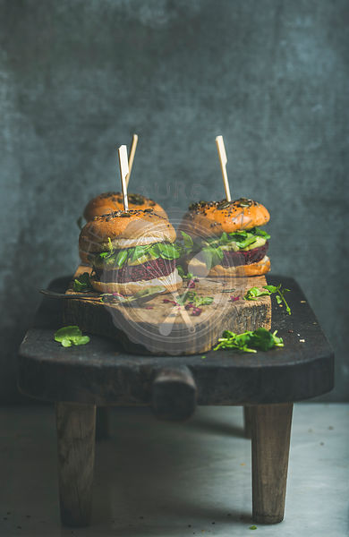 Healthy vegan burgers with beetroot and quinoa patty, arugula, avocado sauce, wholegrain bun on rustic wooden board over dark table, plywood background