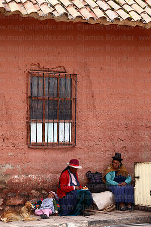 Indigenous women sitting below window of colonial house, Lampa, Peru