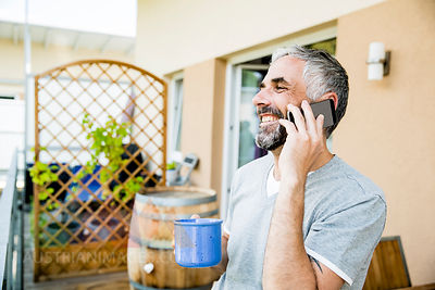 Man on his balcony telephoning with smartphone  holding cup of coffee