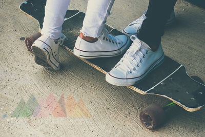 Feet of two teenagers on skateboard