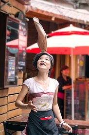 Chinese woman launching round pizza in the air