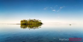 Sunset over small islet with man kayaking, Rarotonga, Cook Islands