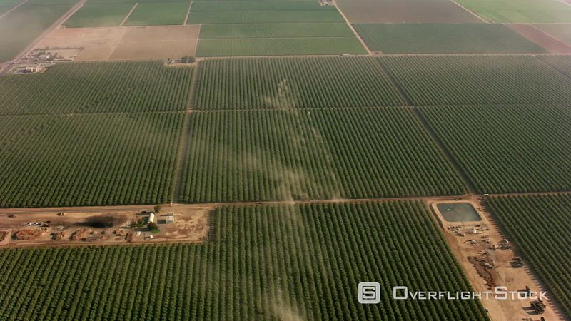 California Aerial shot of orchards with tractors making dust.  Shot with Cineflex and RED EpicW Helium.