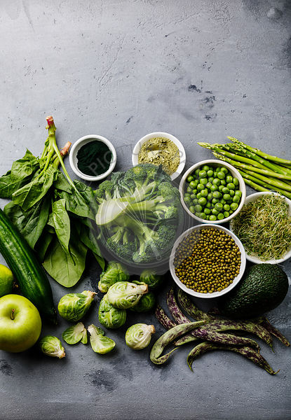 Healthy Green food Clean eating selection Protein source for vegetarians: asparagus, apple, avocado, broccoli, spinach, spirulina, green peas on gray concrete background copy space