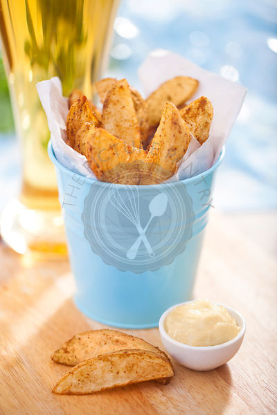 Potato wedges in a bucket with a glass of beer