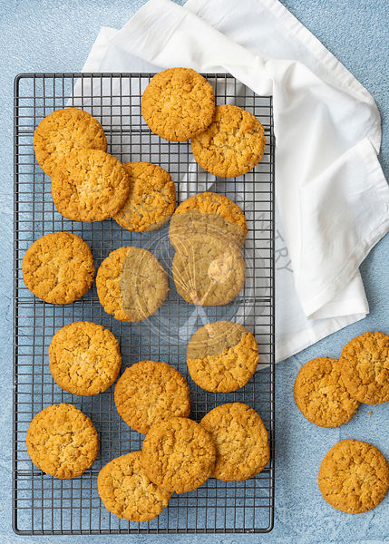 Honey and oatmeal biscuits cooling on a wire rack against a blue background.