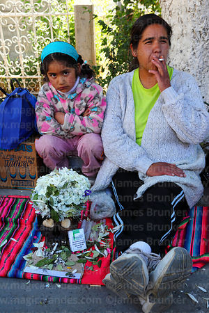 Woman sitting next to skull smoking cigarette, Ñatitas festival, La Paz, Bolivia