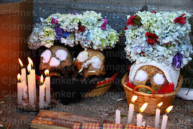 Skulls with burning candle offerings at Ñatitas festival, La Paz, Bolivia