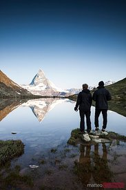 Two hikers looking at Matterhorn reflected in lake at sunrise