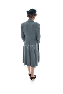 A 1940's woman in a coat, from behind, looking down – shot from eye-level.