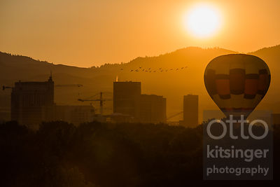 hot air balloon near downtown at sunrise