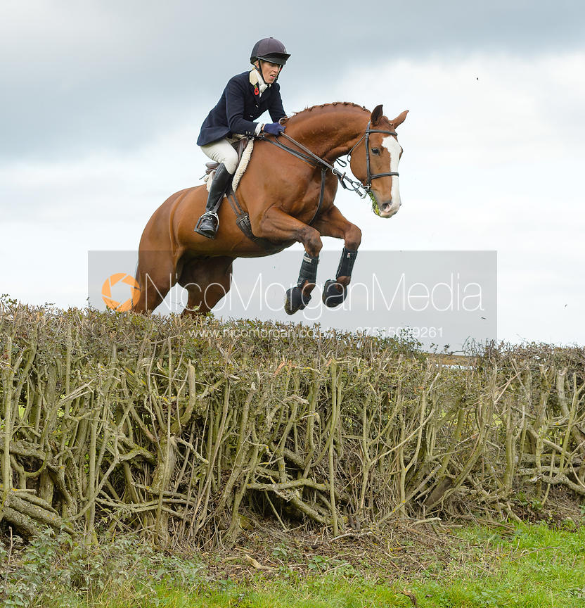 Katie Barber jumping a hedge near Gartree Covert