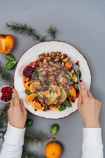 A woman serving a bowl of roasted brussels sprouts salad with carrot, orange, persimmon and pomegranate arils photographed from top view. Brussels sprouts, orange, persimmon and sun-dried tomatoes accompany.