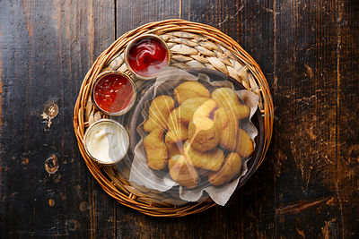 Homemade Chicken breast nuggets with three popular sauces on wooden background