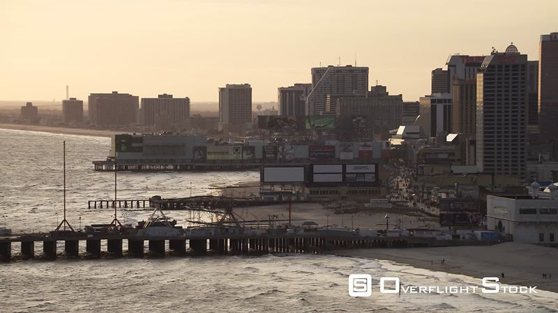 Leaving Atlantic City, New Jersey, looking back at casino resorts and amusement parks on piers along the Boardwalk. Shot in November