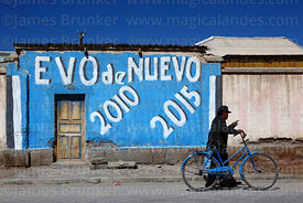 Man pushing bicycle past mural showing support for Evo Morales on house, Uyuni, Bolivia