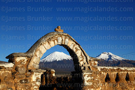 Stone arch entrance to rustic church near Lagunas and Payachatas volcanos, Sajama National Park, Bolivia