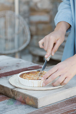 Italy, woman's hands cutting tartlet
