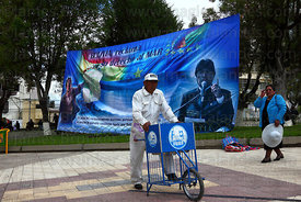 Ice cream seller below banner with president Evo Morales Ayma and Eduardo Avaroa , Plaza Avaroa , La Paz , Bolivia