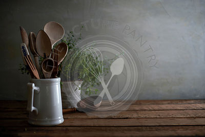 Rustic still life of a kitchen counter with worn wooden utensils in a porcelain pitcher and a lovely tangled oregano plant in the background.