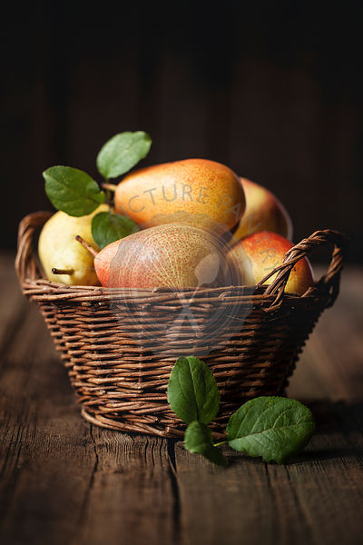 Pears in a basket over dark background