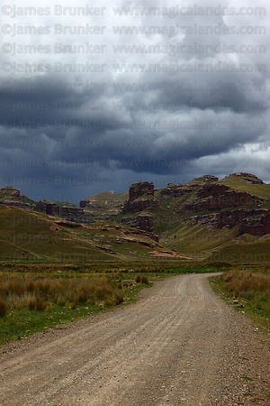 Dirt road approaching Tinajani Canyon and storm clouds in rainy season , near Ayaviri , Puno department , Peru