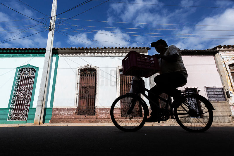 Silhouette of a Man on a Bicycle in a Street in Remedios