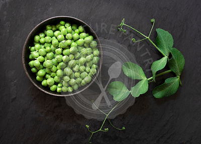 Shelled green peas in a bowl with leaves from the plant.