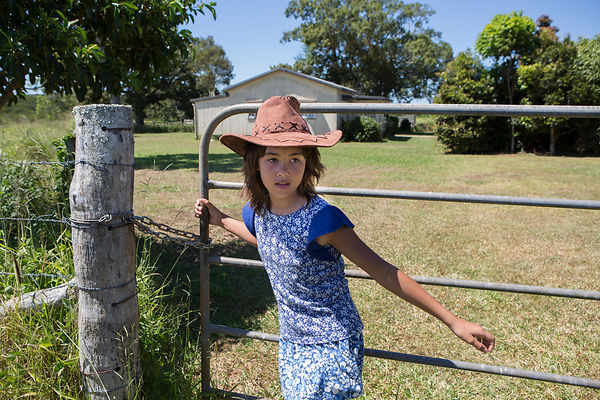 Mizuki, 9 ans referme la porte qui permet d'accéder au terrain où sont les vaches, plateau Atherton, Queensland, Australie / Mizuki, 9-year-old is closing the door to the cows' field, Atherton Plateau, Queensland, Australia