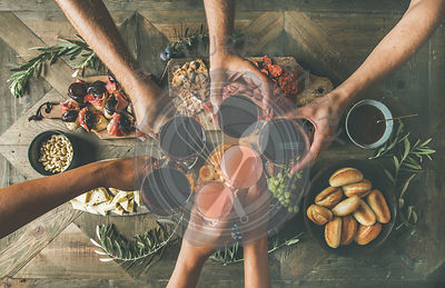 Top view of people having party, gathering, dinner together sitting at wooden table set with wine snacks and fingerfoods