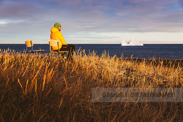 Man sitting on the beach watching the icebergs pass by in Qeqertarsuaq, Greenland
