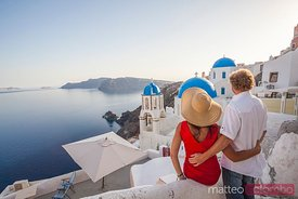 Adult couple watching sunset in Oia, Santorini, Greece