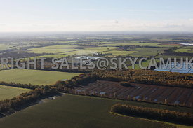 Farming landscape aerial photograph looking across green fields and woodlands displaying their autumnal colours