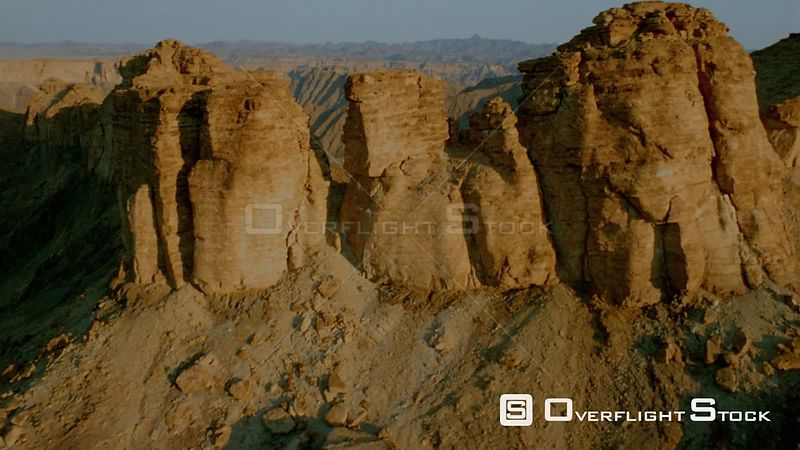 Aerial shot sun shinning on side of mountain and cliff face, over the top and down side of mountain in shadow to wide shot of mountain ranges Fish River Canyon Namibia