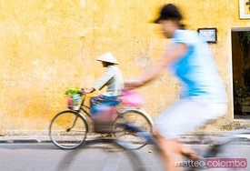 Vietnam, Hoi An. Local people on bicycle in the streets of the town
