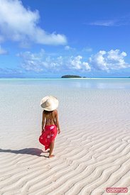 Beautiful woman in front of small island, Aitutaki, Cook Islands