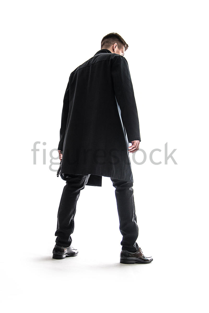 A Figurestock image of a mystery man standing, holding a gun – shot from low level.